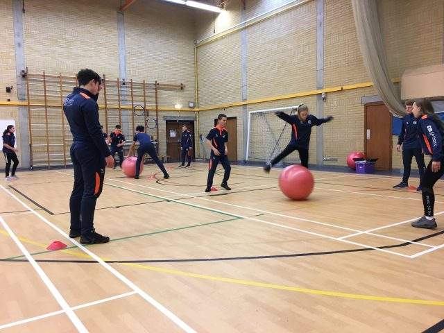 Students in the Sports Hall working with exercise balls